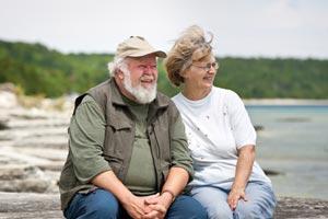 senior couple sitting at beach